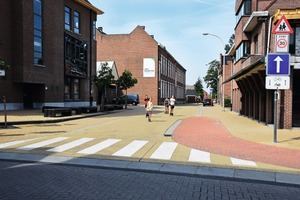 "<div class=""bildtext_en"">Coloured with iron oxide pigments from Cathay Industries, paving stones for a footpath as well as a driving lane mark the calmed traffic zone in this school area</div>"