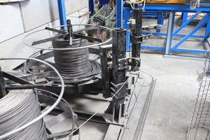 "<div class=""bildtext_en"">View from the back looking at the cage production line - in the foreground the coils with winding wire, behind them, on the right, the blue ESR straightening and cutting machine with the yellow attachment for the feeding of the finished longitudinal bars to the VTA 160 cage welding machine</div>"