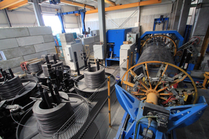 "<div class=""bildtext_en"">View from the front looking at the cage production line - on the left the coils with the longitudinal wires in four different diameters; the wires run to the blue ESR straightening and cutting machine placed behind; the VTA 160 cage welding machine on the right </div>"