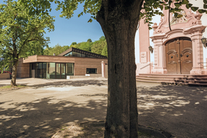 """<div class=""""bildtext_en"""">The new parish hall (at the back left) ideally matching the terrain and the existing buildings</div>"""