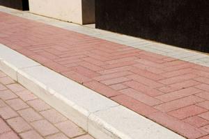 Synthetische Eisenoxidpigmente der Serie Ferrotint erzeugen die leuchtend rosa Farbe, die in der Bodengestaltung dominiert und an die Ziegelfassade der Tourist-Information anknüpft