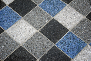 The marbling of the tiles is caused by polished concrete. Black stones are added to the blue-colored concrete and come to the surface after polishing