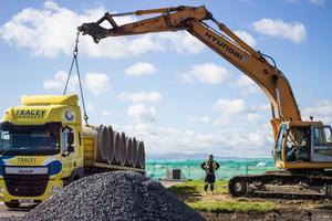 """<div class=""""bildtext_en"""">Unloading concrete pipes at Dublin Airport </div>"""