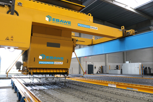 "<div class=""bildtext_en"">The automatic concrete spreader ensures an even and optimized distribution of the concrete into the molds</div>"