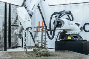 """<div class=""""bildtext"""">Der Kuka Roboter trägt mit gleichmäßigen Bewegungen aus einer großen Düse Spritzbeton auf den Gitterstahlkorb auf</div>"""