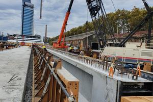 """<div class=""""bildtext"""">Im Fertigteilwerk direkt auf der Baustelle können auf einer 90 m langen Bahn zur Vorspannung gleichzeitig vier Träger hergestellt werden</div>"""