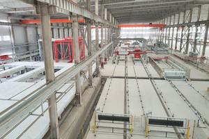"""<div class=""""bildtext"""">Für das Schalen und Entschalen der Paletten wurde eine zweite Ebene installiert. Mit den produzierten Fertigteilen werden mehrstöckige Wohnhäuser in der Provinz Shandong errichtet.</div>"""