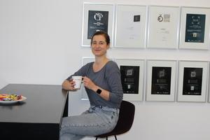 """<div class=""""bildtext"""">BFT-Redakteurin Karla Knitter trinkt Kaffee in der Lounge des Bauverlags</div>"""