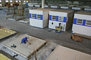 "<div class=""bildtext_en"">The forms for the next casting are being readied in the front area of the production hall, while the completed Fastflex container modules await shipment in the rear of the hall</div>"