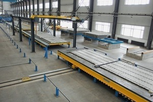The precast floor slabs are lifted in horizontal position for ­being transported into the outdoor storage area by means of transport racks using a run-off carriage with side-shifter