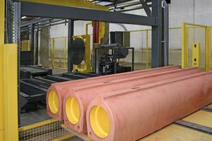 Die entschalten Produkte werden nach einer In-LineVakuumprüfung entsprechend der Nennweite in Paketen auf das Austrageband gestellt und zum Abtransport aus der Halle gefahren<br />