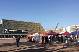 """<div class=""""bildtext_en"""">The main entrance to the fair on a sunny day</div>"""