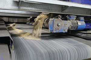 "<div class=""bildtext_en"">The hoppers containing the aggregates for the colored face concrete travel transverse to the movement direction across the belt conveyor transporting the aggregates to the block making machine</div>"