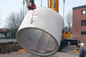 """<div class=""""bildtext"""">Schweres Gerät wurde eingesetzt, um das großkalibrige Stahlbetonrohr der Berding Beton GmbH nach dem Antransport mit einer speziellen Verankerung in die horizontale Verlegeposition zu bringen</div>"""