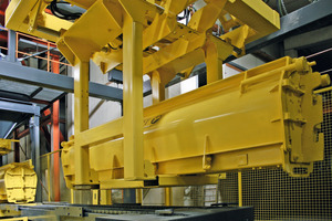 Ein Roboter übernimmt die befüllte Form und stellt sie auf dem vorgesehenen Aushärteplatz ab. Wechselweise wird eine Form mit dem bereits erhärteten Produkt aufgenommen und zum automatischen Entschalen in der Anlage abgesetzt<br />