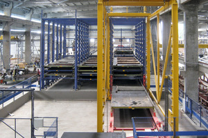 "<div class=""FB BU Zahl"">8</div><div class=""bildunterschrift_en"">Automatic storage and retrieval machine for transferring the pallets into the curing chamber and out again</div>"