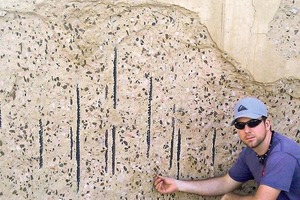 Doktorand Ronald Richter betrachtet eine Betonplatte, die großer Hitze ausgesetzt war