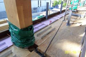 """<div class=""""bildunterschrift_en"""">→ 2 Detailed view of the timber-concrete composite floor: LSL elements with some inserted WCC shear connectors visible on the top side. The insulation panels have also been laid. In the foreground, the image clearly shows the stud shear connectors mounted on the steel beams, which contribute to creating a biaxially restrained floor structure after concrete pouring </div>"""