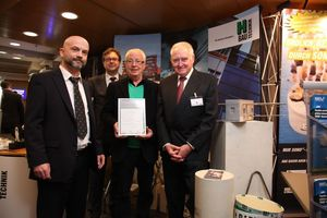 """<div class=""""bildunterschrift_en"""">H-Bau founder Gerhard Horstmann (center) was pleased to receive the award and the congratulations extended by (right to left) Prof. Dr.-Ing. Hans-Wolf Reinhardt, chairman of the jury, Dr. Ulrich Lotz, managing director of the Fachverband Beton- und Fertigteilwerke Baden-Württemberg (Baden-Württemberg Association of Concrete and Precast Plants) and organizer of the BetonTage, and Christian Jahn, BFT International editor-in-chief </div>"""